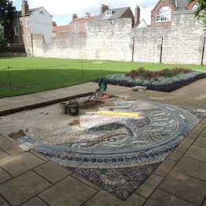 The mosaic map is carefully laid in place.